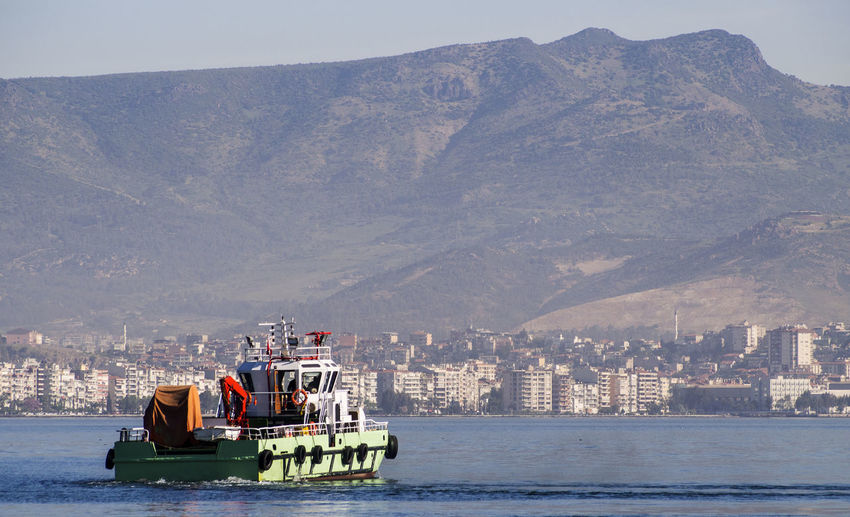 Tugboat on the background of Izmir Beauty In Nature Building Exterior City Cityscape Cruise Ship Culture International Landmark Mountain Mountain Range Nautical Vessel Outdoors Physical Geography Sailing Scenics Sea Tourism Tranquil Scene Tranquility Transportation Travel Travel Destinations Tugboat Vacations Water Waterfront