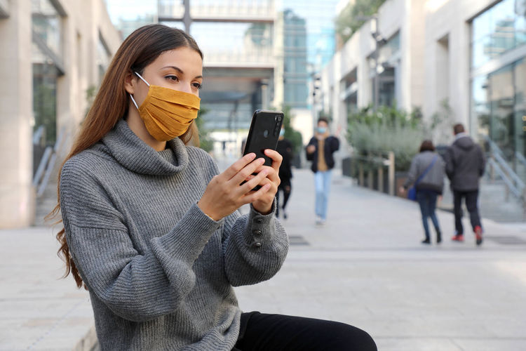 Young woman wearing mask using smart phone while standing on road
