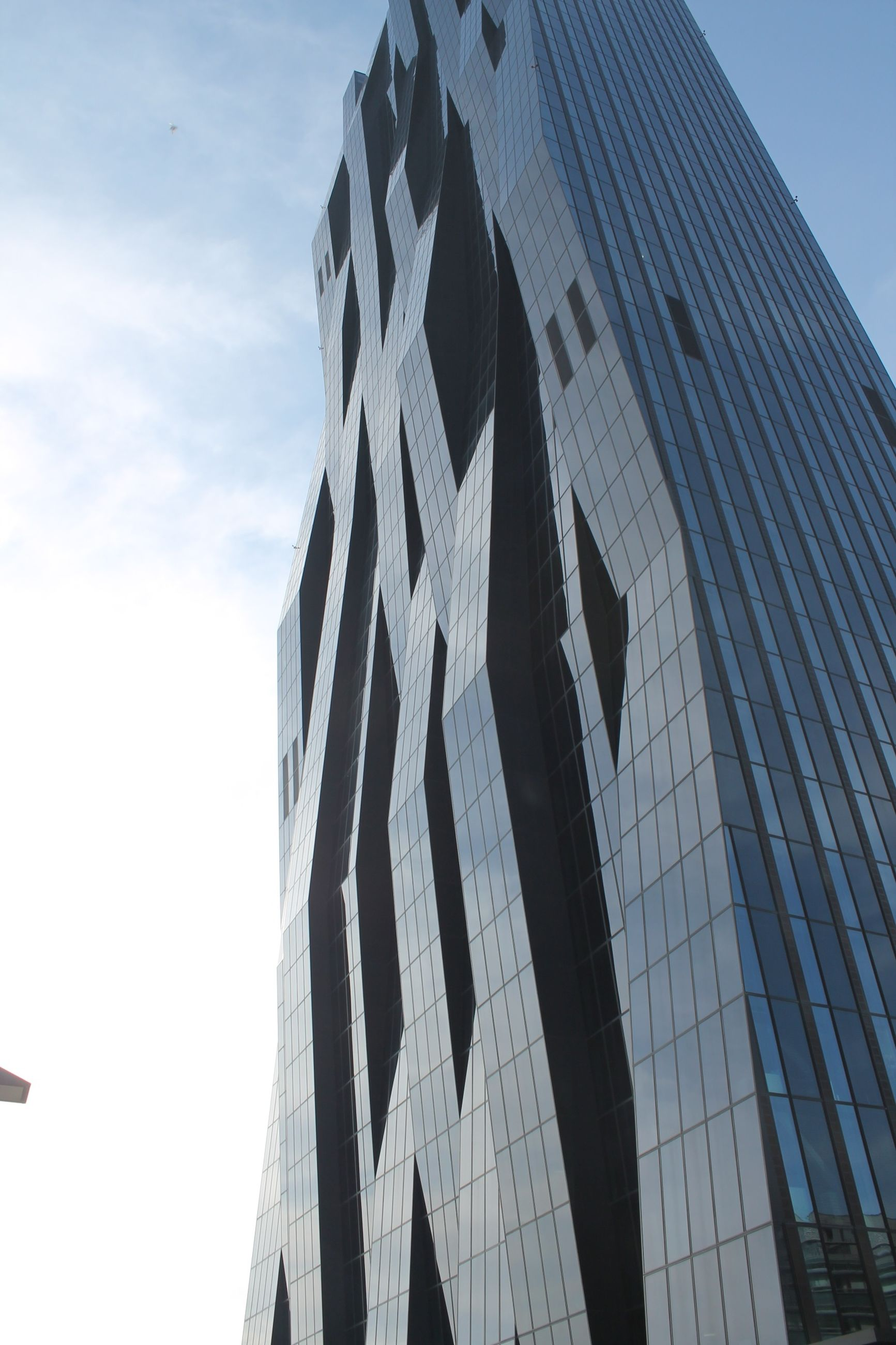 low angle view, building exterior, architecture, built structure, sky, office building, modern, tall - high, skyscraper, building, city, tower, day, outdoors, no people, tall, pattern, clear sky, architectural feature, sunlight