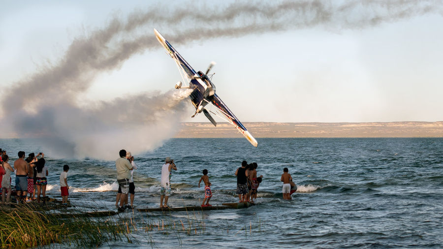 People Standing By Crashing Air Vehicle On Shore Against Sky