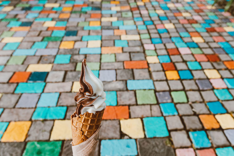 Close-up of ice cream cone against footpath