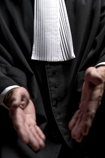 Midsection of lawyer gesturing against black background