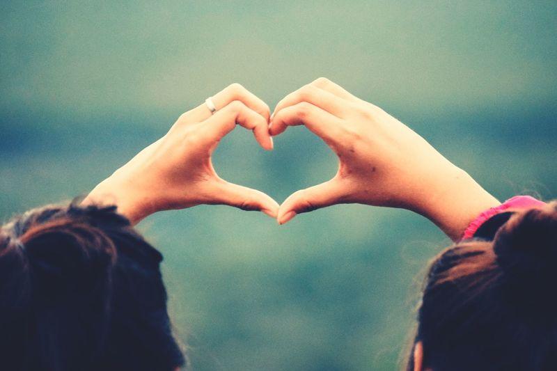 Rear view of couple making heart shape