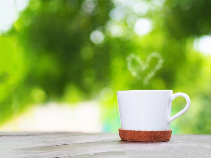 Coffee cup with a shape of heart smoke over green leaf background. Bright Coffee Coffee - Drink Coffee Cup Copy Space Crockery Cup Day Drink Focus On Foreground Food And Drink Green Color Heart Hot Drink Mug No People Non-alcoholic Beverage Outdoors Refreshment Smoke - Physical Structure Table Tea Tea Cup Tree Wood - Material