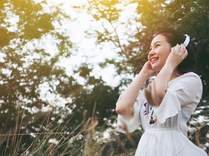 Happy Asian woman listen her favorite song in the garden. Music Adult Adults Only Day Happiness Holding Low Angle View Nature One Person One Woman Only One Young Woman Only Outdoors People Smiling Standing Tree Young Adult Young Women