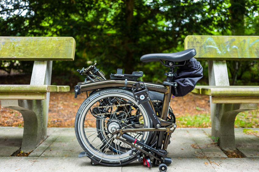 Brompton Black Lacquer edition in Hamburg Brompton Absence Close-up Day Focus On Foreground Green Color Land Land Vehicle Mode Of Transportation Nature No People Outdoors Park Park - Man Made Space Plant Stationary Sunlight Transportation Tree Wheel Wood - Material