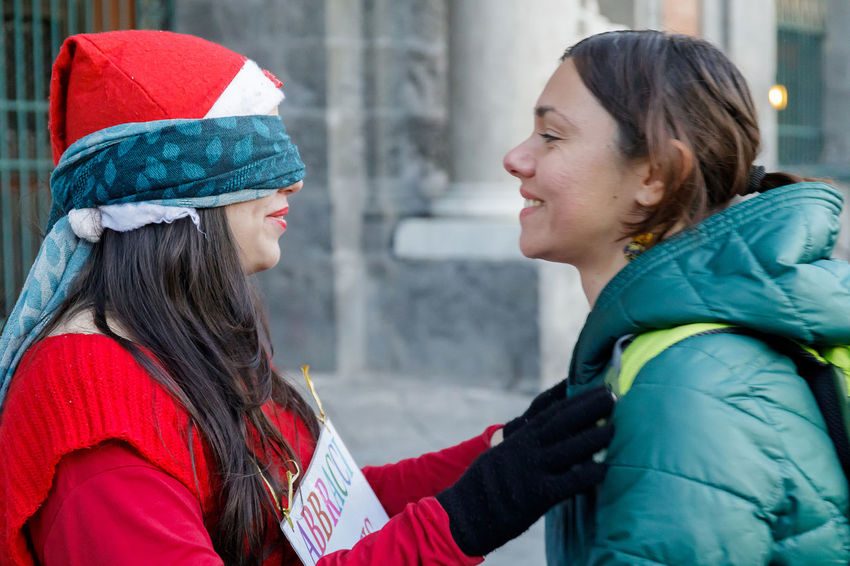 Naples, Italy - December 16, 2018: Piazza del Plebiscito, tourist hugs a Santa Claus on the street in a sign of solidarity and peace. We are in the Christmas period. Young Women Clothing Women Adult Two People Headshot Side View Real People Young Adult Females Focus On Foreground Portrait Warm Clothing Hat People Lifestyles Togetherness Winter Day Hairstyle Daughter Outdoors Profile View Christmas
