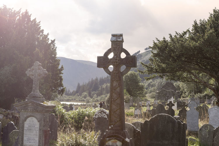Old Celtic Cross in The Glendalough s Cemetery. Wicklow mountain, Ireland Glendalough Celtic Irish Cross Gravestone Ireland Religion Belief Spirituality Sky Nature Architecture Grave Cloud - Sky Cemetery The Past Landmark Graveyard Headstone Historic Medieval Old Stone Sunset Tombstone Tomb