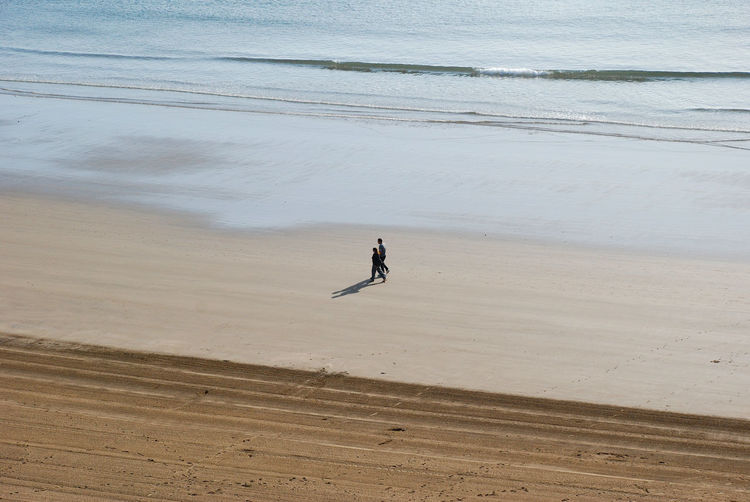Two people walking on beach