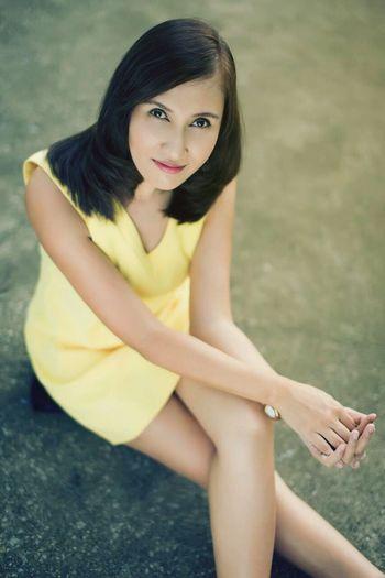 High angle portrait of beautiful woman sitting on walkway