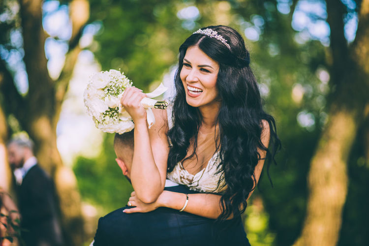 Smiling bride holding bouquet