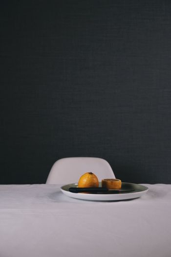 Oranges in plate on table against wall