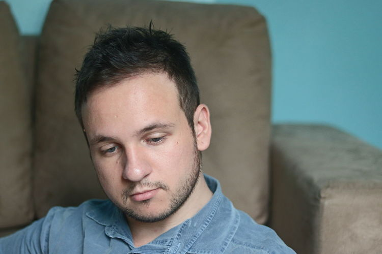 Headshot Portrait One Person Front View Young Adult Indoors  Lifestyles Casual Clothing Young Men Beard Relaxation Focus On Foreground Sofa Looking At Camera Real People Looking Adult Sitting Contemplation