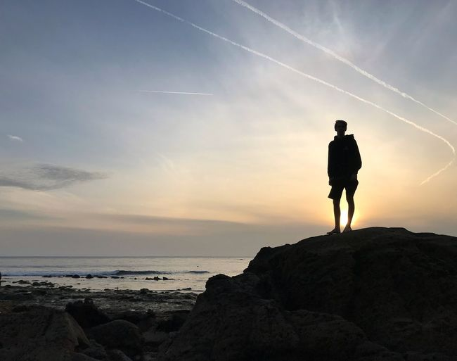 Silhouette man standing on rock at beach against sky during sunset