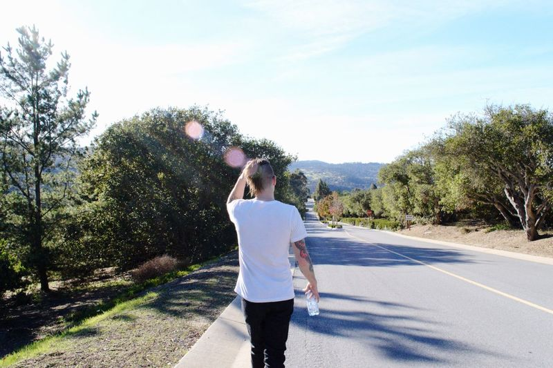 Walking Down Road Lens Flare White T Shirt Man Wearing Basic White T Shirt Black Jean Man Hillscape Hillscape United States California Plant Tree Real People Nature One Person Road Sky Casual Clothing Sunlight Leisure Activity Day Lifestyles Rear View Outdoors