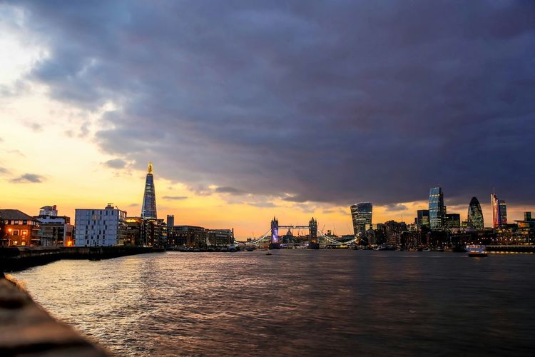 View of thames river amidst city against cloudy sky at dusk