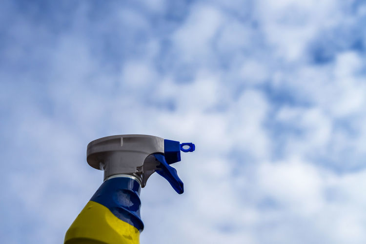 Low angle view of bottle against cloudy sky