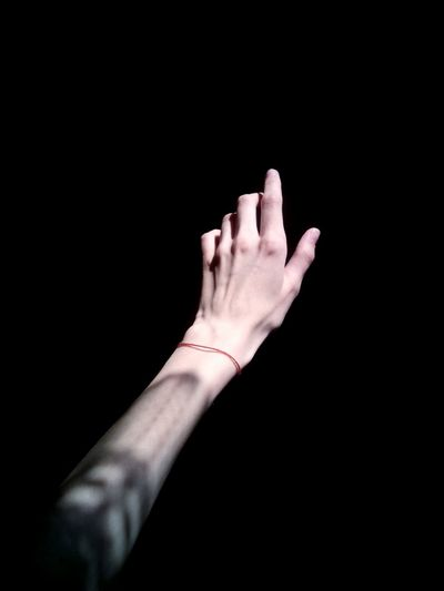 Cropped image of hand against black background
