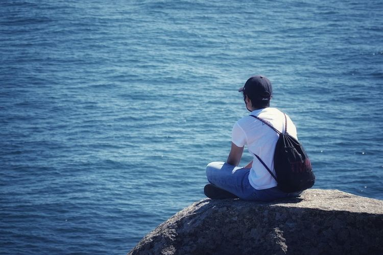 Rear view of man sitting on rock looking at sea