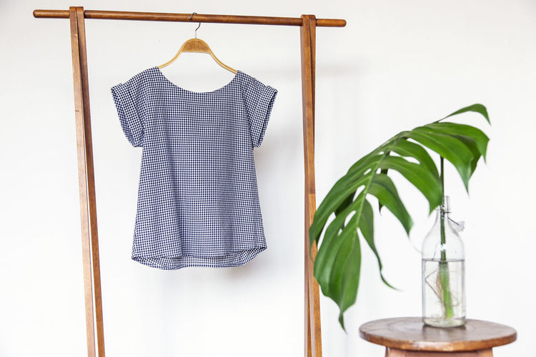 Woman blouse with blue blouse cotton on wooden hangers. Indoors  Hanging No People Leaf Clothing Plant Part Still Life Close-up Plant Wood - Material Nature Coathanger Wall - Building Feature White Color Green Color Textile White Background Fashion Home Interior Absence Clean Blue Blouse Blouse Beige Plant Decoration