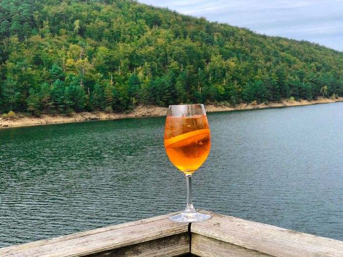 Glass of aperol spritz cocktail with lake and green forest in the background Summer Drink Summer Celebrate Cheers No People Nobody Nature Day Landscape Idyllic Trees Forest Water Lake Cocktail Orange Slice Orange Color Aperol Aperol Spritz Drinking Straw Straw Beverage Alcoholic Drink One Glass Drinking Glass Alcohol Refreshment Outdoors Freshness