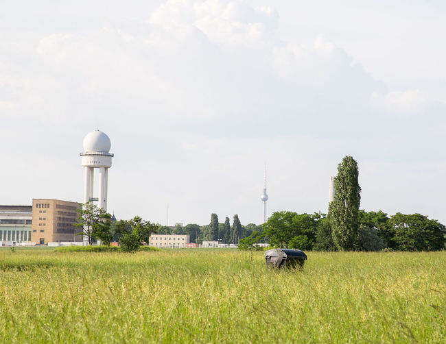 Control tower at airport in city against sky seen from tempelhofer feld park