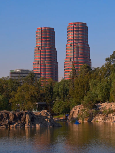"""View of the residential towers """"Residencial del Bosque"""" and the main lake in Chapultepec Park, Mexico City, Mexico. Architecture Exterior Mexico Mexico City Architecture Beauty In Nature Building Building Exterior Buildings Chapultepec Chapultepec CDMX Clear Sky Day Nature Outdoors River Scenics Sky Tree Water Waterfront"""