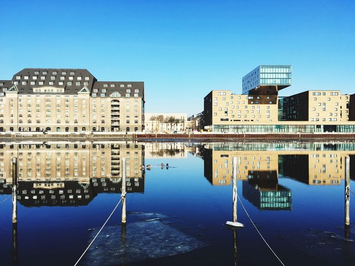 Reflection Of Buildings In City Against Clear Blue Sky