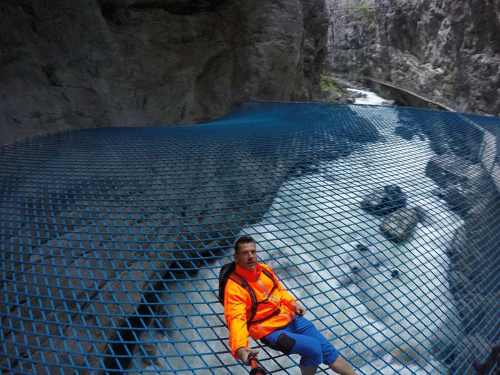 High angle portrait of mature man on net over river amidst rock formations