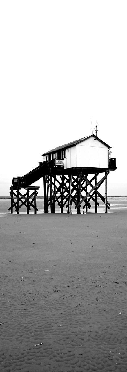 sea, built structure, copy space, silhouette, water, beach, clear sky, horizon over water, sand, architecture, outdoors, no people, nature, scenics, day, beauty in nature, sky