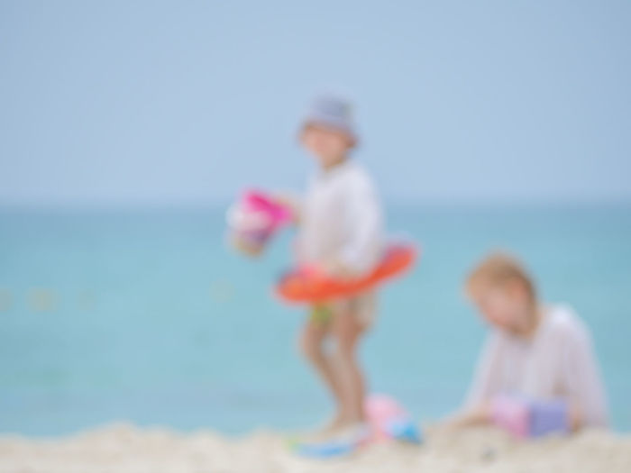 Low angle view of children on beach against sky