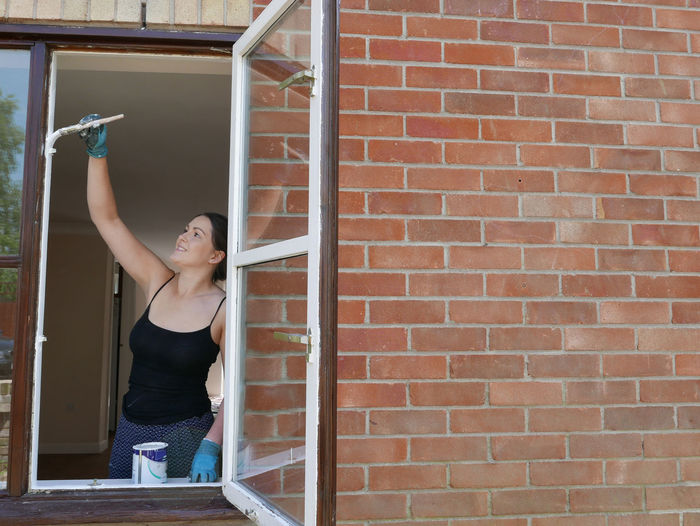 Smiling young woman painting window frame