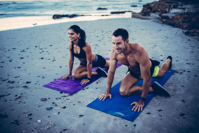 Adult Athlete Beach Exercising Fitness Fitness Couple Fitness Training Friendship Full Length Healthy Lifestyle Leisure Activity Lifestyles Men Recreational Pursuit Relaxation Exercise Sitting Sport Sports Sports Training Stretching Summer Togetherness Warm Up Young Adult Young Women