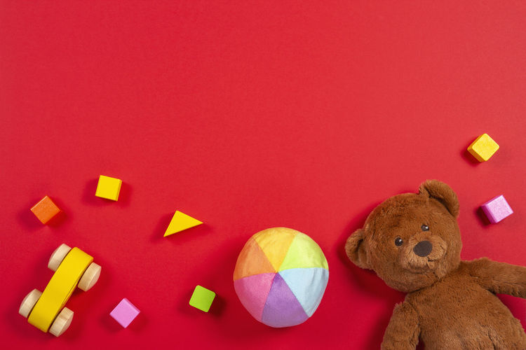 Directly Above Shot Of Colorful Toys Against Red Background