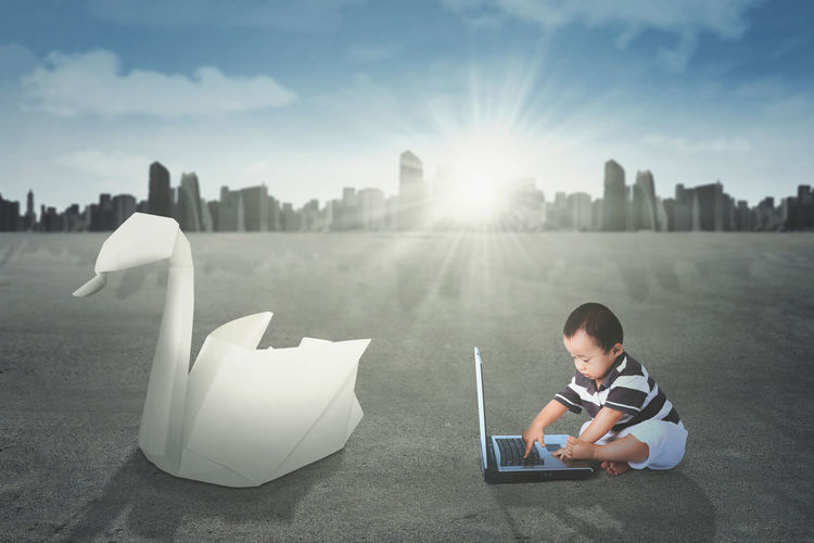 Digital composite image of baby boy using laptop on road against sky in city during sunny day