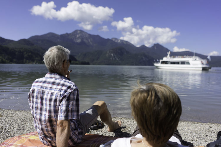 Rear view of senior couple looking at ship in kochelsee