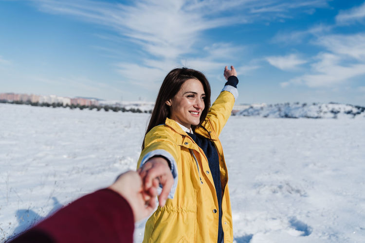 Portrait of smiling woman standing at beach during winter