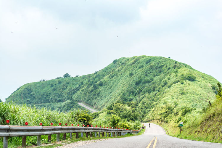 Road Transportation Sky Green Color Mountain Plant Nature Beauty In Nature Direction Scenics - Nature Day Tree The Way Forward Tranquility Tranquil Scene No People Environment Non-urban Scene Sign Country Road Outdoors