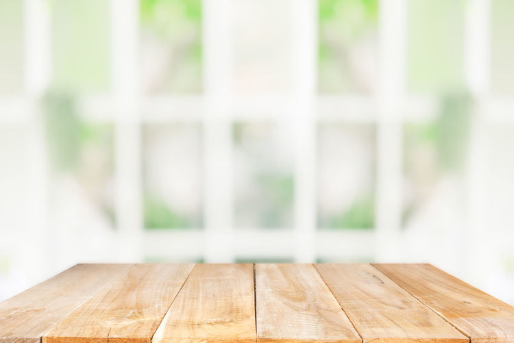 Close-up of wooden table against window