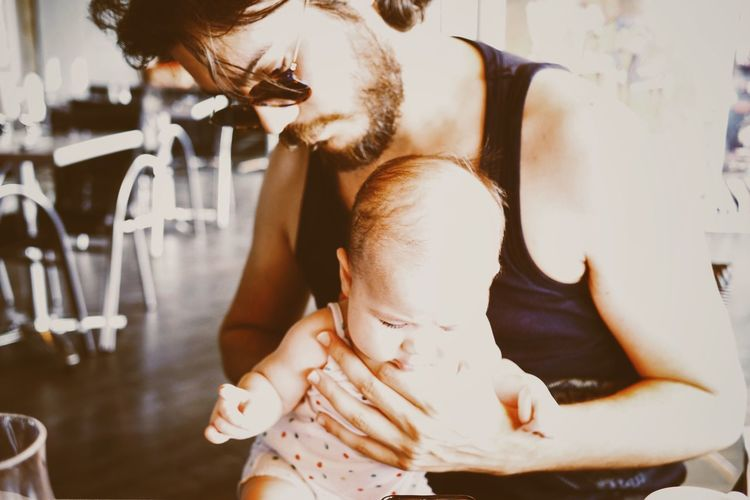 Father Holding Baby Girl In Restaurant