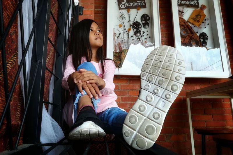 Full length of girl sitting at home