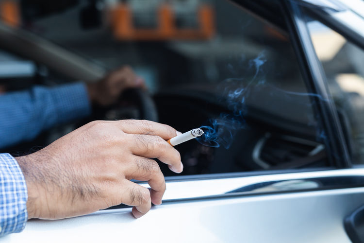 Man holding cigarette in car