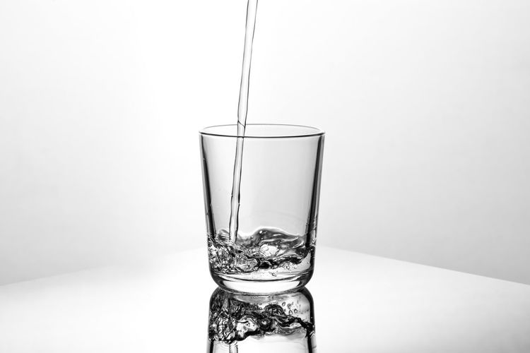 Close-up of glass pouring water against white background