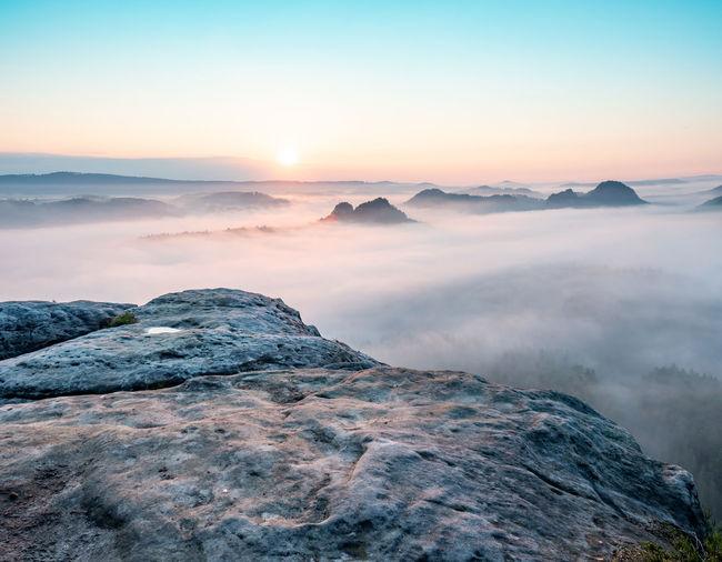Mountain top rock, sleepy misty landscape bellow under heavy morning fog