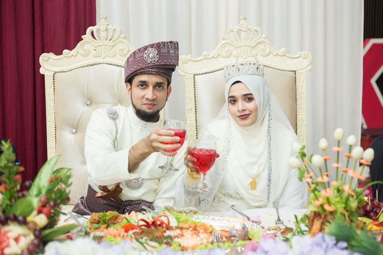 Portrait Of Bride And Bridegroom Holding Drink Glasses