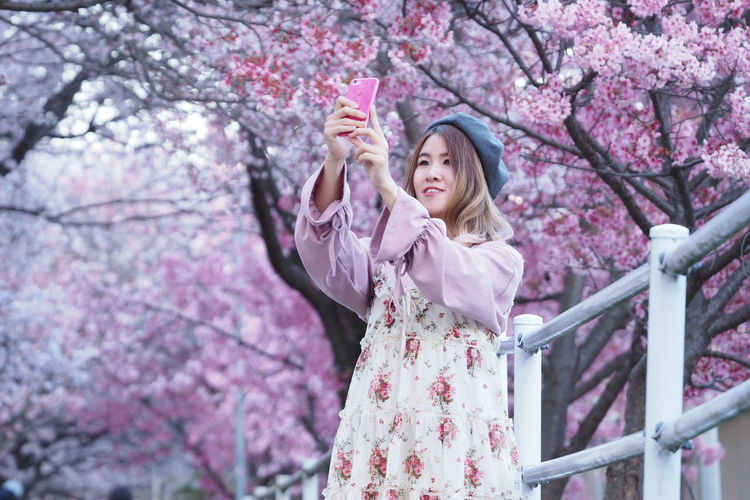 Beauty In Nature Blossom Branch Cherry Blossom Cherry Tree Day Flower Fragility Kimono Lifestyles Low Angle View Nature One Person One Young Woman Only Outdoors Park - Man Made Space Petal Pink Color Real People Sakura Springtime Travel Destinations Tree Young Adult Young Women