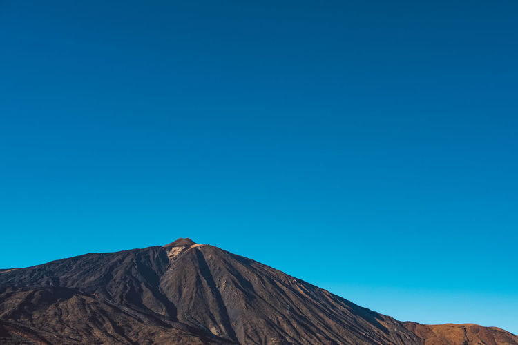 View of volcanic mountain against blue sky