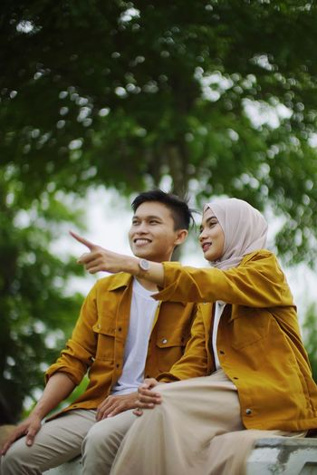 Young couple looking away while sitting against blurred background