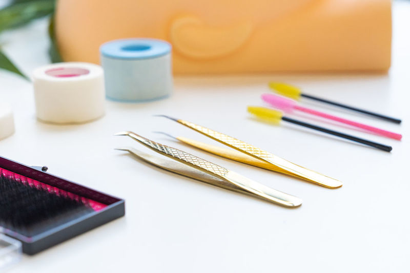 Close-up of false eyelashes with tweezers and curlers on table