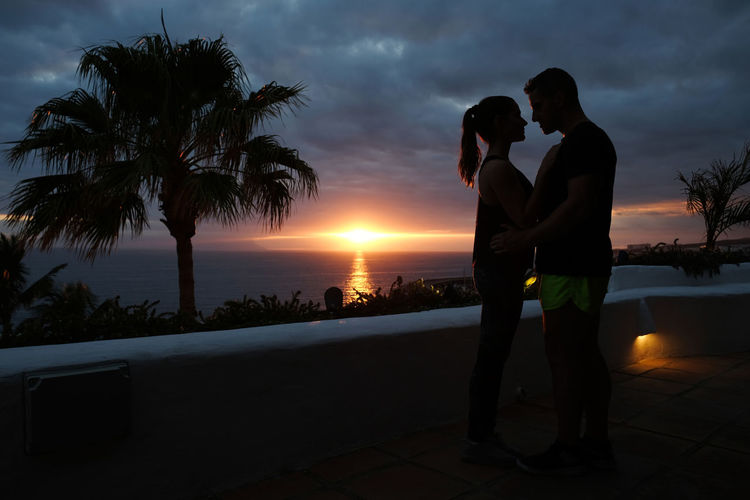 Couple embracing while standing against sky during sunset
